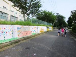 いちょう小学校の壁面に各国を象徴する絵とあいさつを描いた「あいさつロード」